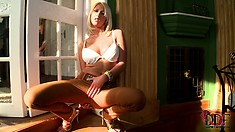 The seductive blonde stands by the window showing off the sexy contours of her body